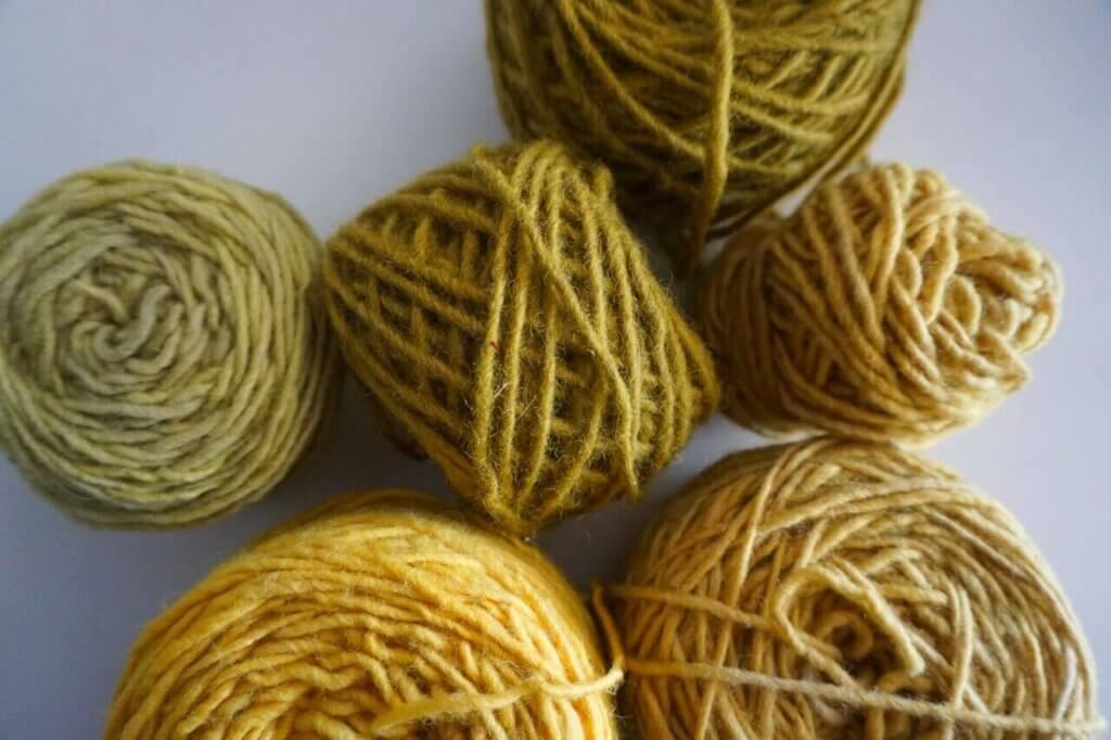 Balls of yarn dyed naturally in yellows and greens from onion skins.