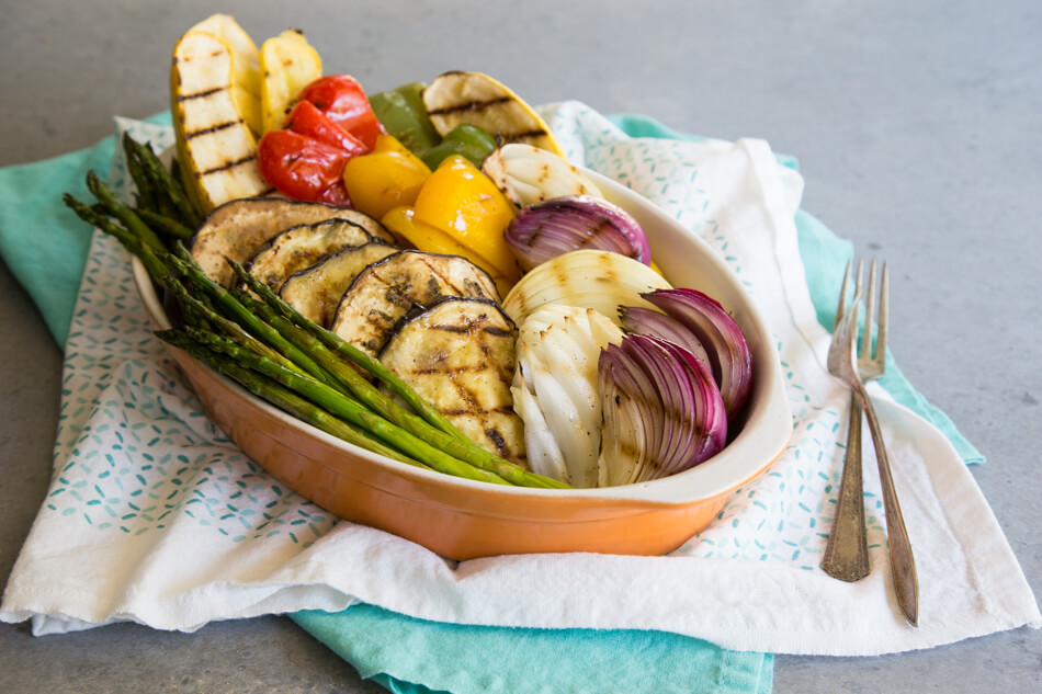 Grilled vegetables stacked in a casserole dish