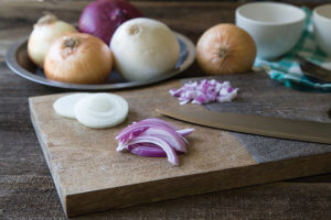 sliced onions on a cutting board with a knife