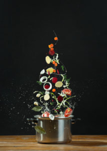 Vegetables on a black background  tossed into a pot
