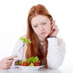 Girl with fork in salad